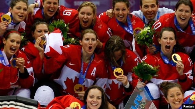 Team Canada players pose with their gold medals during the presentation ceremony after Canada defeated Team USA in overtime in the women's ice hockey final game at the 2014 Sochi Winter Olympics, Feb. 20, 2014.