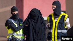 FILE - Masked Spanish police officers lead a detained woman in Melilla, Dec. 16, 2014. Arrest was part of ongoing swoop on suspected efforts to recruit women to go to Syria and Iraq to support Islamic State insurgents.