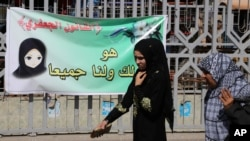 FILE - Females pass by a banner in Baghdad, Iraq, March 13, 2014.