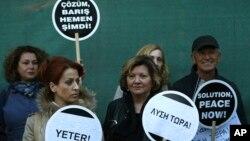 "Warga Siprus keturunan Yunani dan Turki memegang slogan berbahasa Yunani, Turki, dan Inggris yang berbunyi ""Solusi Sekarang"" sambil berdiri di depan gerbang utama Istana Ledras, di dalam zona penyangga PBB, dimana utusan PBB akan menjadi tuan rumah dalam acara makan malam dengan para pemimpin rival Siprus yang terbelah di ibukota Sipurs, Nikosia hari Minggu, 2 April 2017 (foto: AP Photo/Petros Karadjias)"