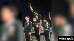 1968年10月16日,參加奧林匹克運動會的美國短跑運動員托米‧史密斯和約翰‧卡洛斯舉起拳頭,抗議非洲裔美國人遭受的不平等待遇。