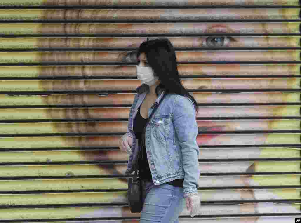 یک زن جوان با ماسک از مقابل یک فروشگاه تعطیل در مرکز لندن عبور میکند. صادق خان شهردار پایتخت انگلیس از مردم خواسته است در بیرون از خانه حتما از ماسک استفاده کنند.