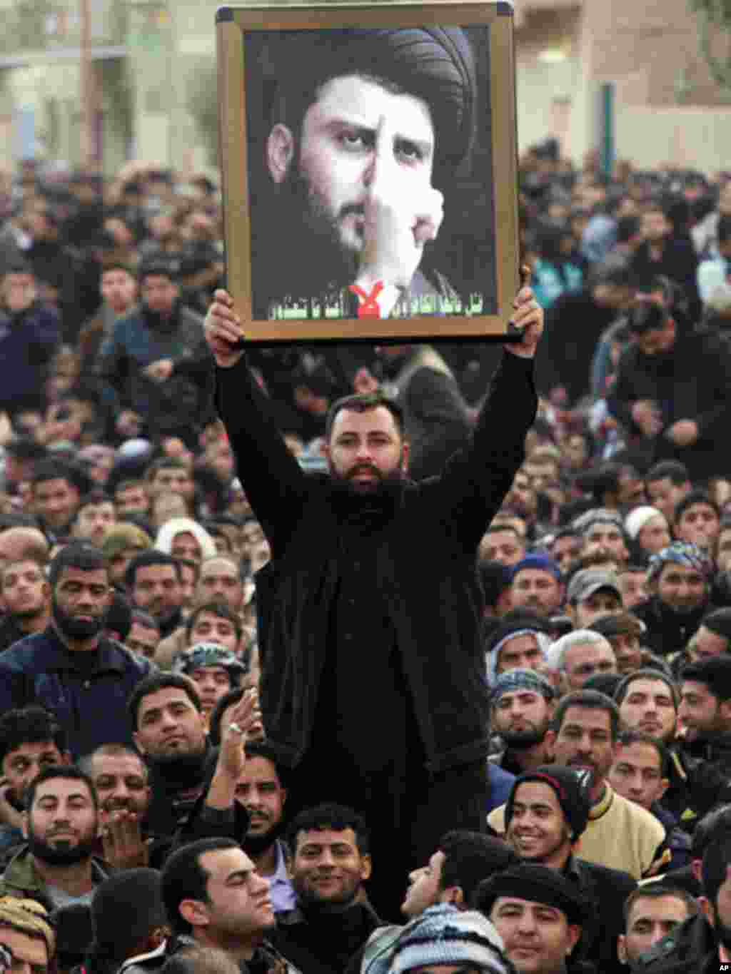 A man holds up Sadrs photograph as faithful gather to watch the cleric's first public appearance since returning from nearly four years of self-imposed exile in Najaf on January 8, 2011. (AP)