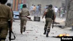 Indian police chase protesters during a strike called by separatists against the recent killings in Kashmir, Sept. 21, 2013.