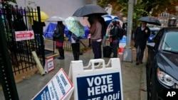 Los votantes se alinean bajo la lluvia en las afueras de Bright Family and Youth Center en el vecindario de Columbia Heights en Washington, el martes 6 de noviembre de 2018.