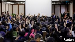 Para anggota keluarga penumpang pesawat Malaysia Airlines penerbangan MH370 melakukan pemunguntan suara untuk berbicara langsung pada wakil pemerintah Malaysia di Lido Hotel di Beijing (17/3).