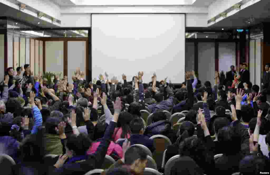 Family members of passengers onboard Malaysia Airlines Flight MH370 vote to talk directly to Malaysian government's representatives during a meeting with the airline's representatives at Lido Hotel in Beijing March 17, 2014.