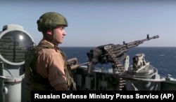 A Russian seaman stands next to a machine gun on the Russian missile cruiser Moskva, near the shore of Syria's province of Latakia, Nov. 27, 2015.