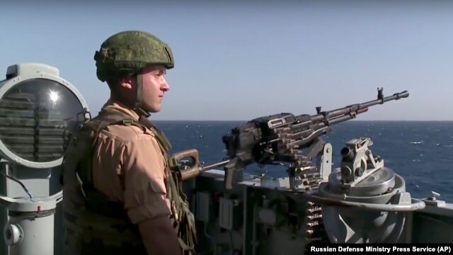 FILE - A Russian seaman stands next to a machine gun on the Russian missile cruiser Moskva, near the shore of Syria's province of Latakia, Syria, Nov. 27, 2015.