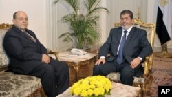 In this photo released by the Egyptian Presidency, President Mohamed Morsi, right, poses for a photograph with his new Prosecutor General, Talaat Abdullah, left, in Cairo, Egypt, Thursday, Nov. 22, 2012.