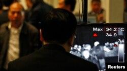 Hành khách đi qua nơi kiểm tra thân nhiệt bằng máy chụp hình hồng ngoại tuyến.