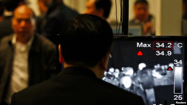 An airport security personnel looks at the screen showing body temperatures scan of arriving travellers at Hong Kong International Airport, Apr. 9,2013.