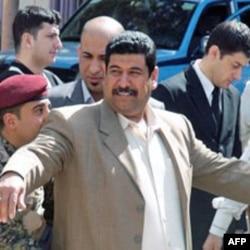 一巴格达选民在进入投票站前接受检查