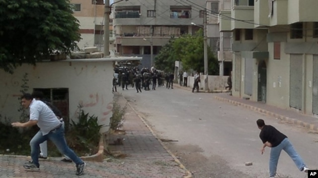 Men throw stones at riot police during clashes in the Mediterranean coastal town of Banias, May 27, 2011.