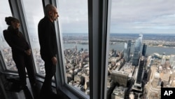 Tom Hennes, right, designer of the 102nd floor observatory of the Empire State Building, looks toward the west view, Thursday, Oct. 10, 2019. (AP Photo/Richard Drew)