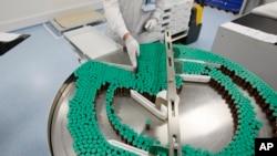 FILE - Laboratory technician at a Sanofi-Pasteur production plant manufacturing Panenza, Val-de-Reuil, western Paris.
