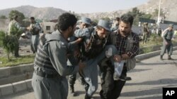 Afghan security forces carry a wounded police man at the site of a suicide attack outside The British Council in Kabul, Afghanistan, August 19, 2011