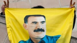 FILE - A Kurdish demonstrator holds a flag with a portrait of jailed Kurdistan Workers Party (PKK) leader Abdullah Ocalan in Strasbourg, France, Feb.14, 2009.