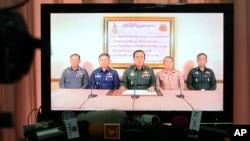 មេបញ្ជាការកងទ័ពថៃ ឧត្តមសេនីយ៍ ប្រាយុទ្ធ ចាន់-អូចា (Prayuth Chan-ocha) (កណ្តាល) អមដោយមន្ត្រីយោធាជាន់ខ្ពស់ផ្សេងទៀត បង្ហាញខ្លួនតាមកញ្ចក់ទូរទស្សន៍ ដើម្បីប្រកាសអំពីការចូលកាន់កាប់អំណាចរបស់យោធាកាលពីថ្ងៃព្រហស្បតិ៍ទី២២ខែឧសភា ឆ្នាំ២០១៤។