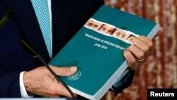 Ngoại trưởng Hoa Kỳ John Kerry cầm một bản sao của phúc trình năm 2016 về nạn buôn bán người (TIP) trong buổi lễ vinh danh những anh hùng TIP tại Bộ Ngoại giao ở Washington, ngày 30 tháng 6 năm 2016.