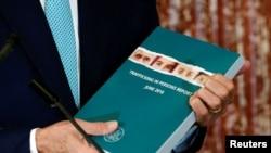 Menteri Luar Negeri AS John Kerry memegang laporan perdagangan manusia 2016 dalam upacara peluncuran di Departemen Luar Negeri di Washington (30/6). (Reuters/Kevin Lamarque)