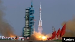 FILE - A rocket loaded with a Shenzhou-9 manned spacecraft lifts off from its launch pad at the Jiuquan Satellite Launch Center, Gansu province June 16, 2012.
