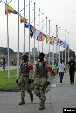 Security guards walk past national flags at dusk at the Francophone Summit in the Democratic Republic of Congo's capital Kinshasa, October 10, 2012.