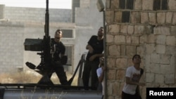 Varios rebeldes del Ejército Sirio Libre durante un bombardeo aéreo en Tel Rafat, al norte de Alepo, el pasado 9 de agosto.