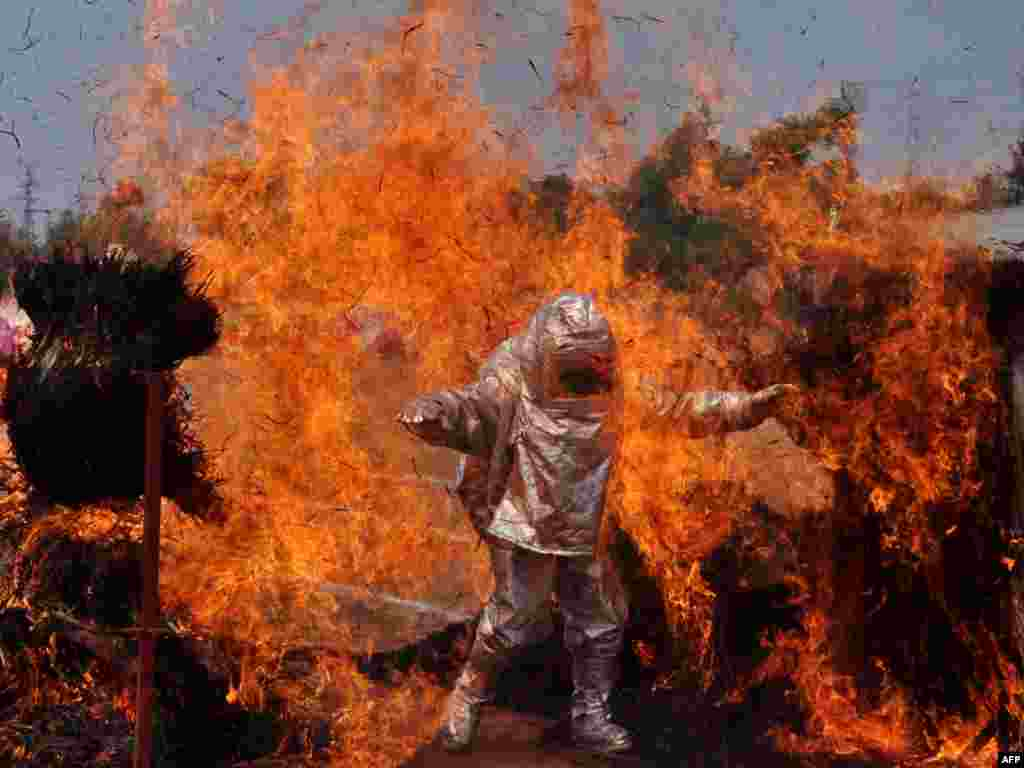 An Indian firefighter wearing a fire proximity suit walks through a wall of flames during a demonstration of firefighting skills for Fire Safety Week in Bhubaneswar. Fire Safety Week runs April 14-20 across India.