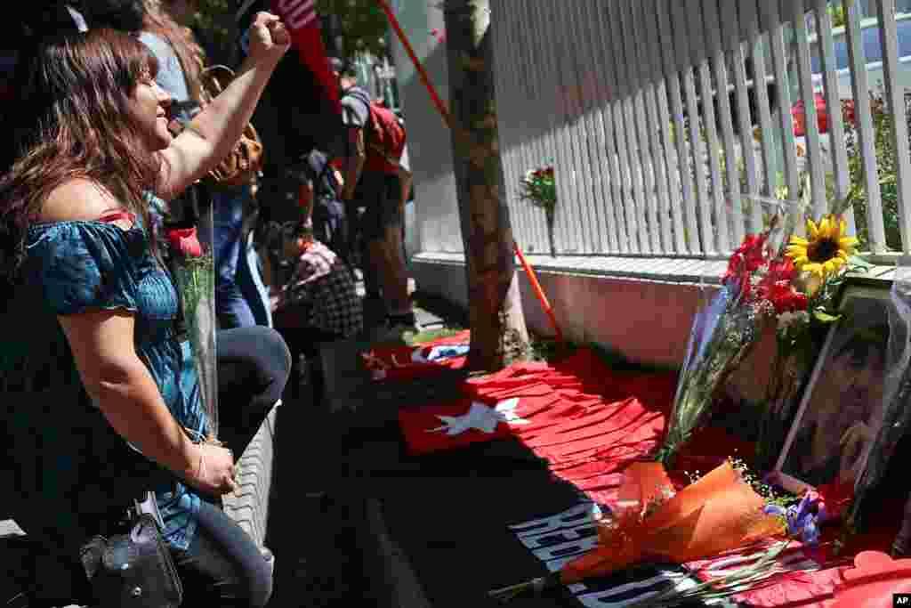 Una mujer levanta el puño ante una foto de Fidel Castro después de colocar una flor en la embajada de Cuba en Santiago, Chile, el sábado 26 de noviembre de 2016.