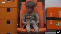 시리아 반군 매체 알레포 미디어 센터(AMC)가 공개한 영상에서 캡쳐한 현지 어린이의 모습. 17일 단행된 공습으로 부상을 입은 이 어린이는 건물 잔해 속에서 구출됐다.