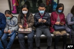People wear masks on a train on the first day of the Lunar New Year of the Rat in Hong Kong on January 25, 2020, as a preventative measure following a coronavirus outbreak which began in the Chinese city of Wuhan.