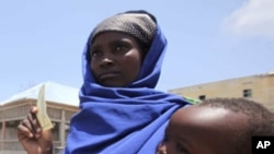 An internally displaced Somali woman carries her child as they wait to receive food aid at a distribution centre at Badbaado settlement camp in Somalia's capital Mogadishu, August 18, 2011