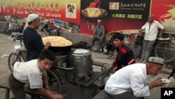 FILE - Uighurs rest near a food stall and Beijing Olympic Games billboards in Kashgar in China's western Xinjiang province, Aug. 6, 2008. Human Rights Watch said Tuesday, May 16, 2017, that China appears to be laying the groundwork for the mass collection of DNA samples from residents in a restive region with a large Muslim population.