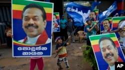 斯里兰卡前总统及议员候选人拉贾帕克萨的支持者举着他的画像,庆祝科伦坡投票的结束。(2015年8月17日)