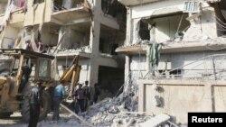 敘利亞居民在被指稱遭敘利亞空軍砲彈擊毀的建築前
