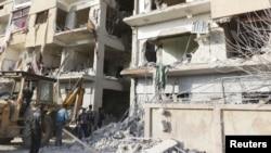 Warga berjalan di dekat bangunan yang hancur pasca serangan pesawat tempur Suriah dari pasukan pendukung Presiden Bashar al-Assad (Foto: dok). Paukan pemerintah Suriah terus menggempur wilayah di sekitar Damaskus untuk mencegah pemberontak mendekati ibukota (3/12).