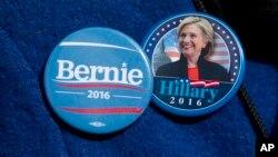 Algunos votantes demócratas usan distintivos de ambos candidatos a la nominación presidencial, Bernie Sanders y Hillary Clinton.