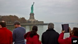 FILE - Tourists view the Statue of Liberty during a ferry ride to Liberty Island in New York, Nov. 5, 2015.