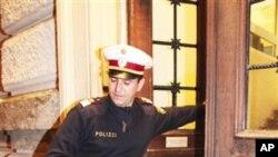Austrijski policajac unosi u sudnicu odjeću bivšeg hrvatskog premijera u petak 10. prosinca