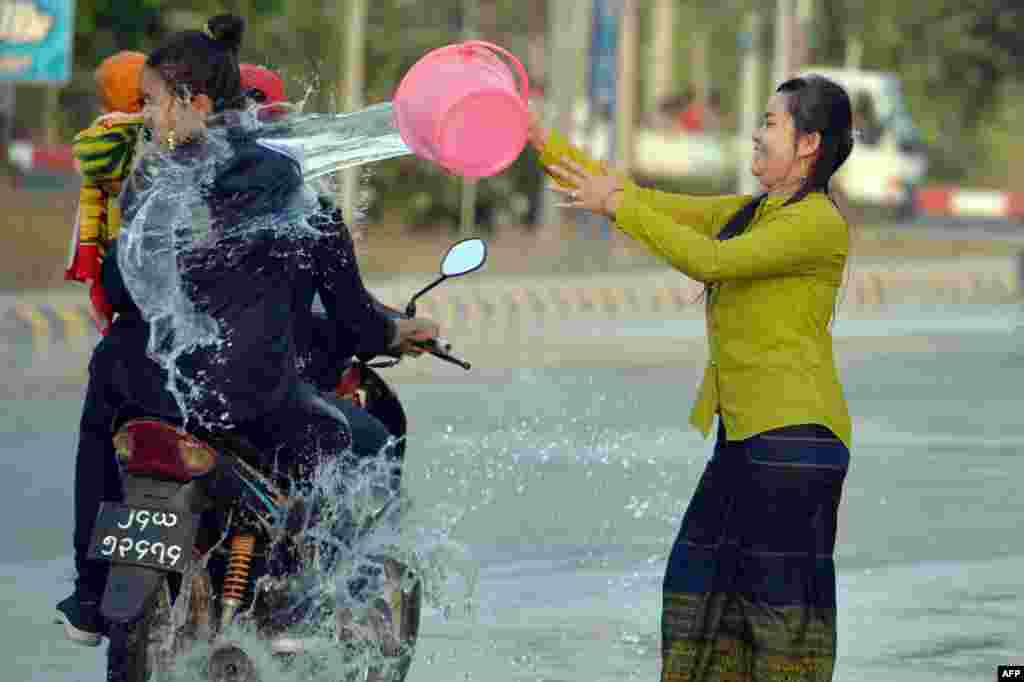 A woman throws water at passing motorists during celebrations for the Thingyan festival, also known as the Buddhist New Year, in Naypyidaw, Myanmar.