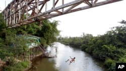 FILE - A youth jumps from an overpass into a river in Paragominas, northern state of Para, Brazil, Sept. 22, 2011. A Brazilian judge on Wednesday granted an injunction blocking a decree by President Michel Temer that opens up a vast Amazon area to mining.