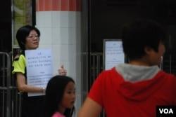 城門谷公共游泳池職員向泳客展示,因救生員人手不足需要關閉的告示(美國之音湯惠芸攝)