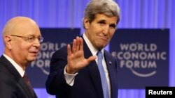 El secretario John Kerry saluda a su llegada a la reunión del Foro de Davos, acompañado de su presidente, Klaus Schwab.