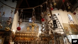 In this Wednesday, Dec. 5, 2018 photo, a worker cleans the dust from a chandelier at the Church of the Nativity, built atop the site where Christians believe Jesus Christ was born, in the West Bank City of Bethlehem. (AP Photo/Majdi Mohammed)