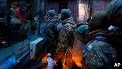 Volunteers from the Azov battalion get on a bus in Kyiv bound for the eastern part of Ukraine to join the fighting against pro-Russian separatists, Jan. 17, 2015.