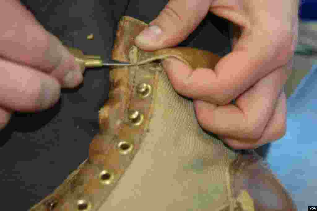 Delicate work to remove the collar which had to be replaced at the Danner factory in Portland, Oregon, Jan. 20, 2014. (Steve Herman/VOA)