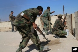 FILE - Syrian soldiers fire return fire, repelling an attack in Achan, Hama province, Syria, Oct. 11, 2015.