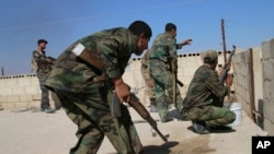 FILE - In this photo taken on Oct. 11, 2015, Syrian soldiers fire repelling an attack in Achan, Hama province, Syria.