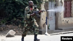 A soldier fires an AK-47 rifle during a protest against President Pierre Nkurunziza and his bid for a third term, in Bujumbura, Burundi, May 25, 2015.